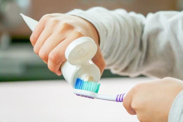 Criança aplicar escova de dentes e creme dental no fundo desfocado Foto Premium