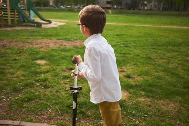 Criança, aprendizagem, para, passeio, um, scooter, em, um, cidade, parque, cute preschooler, menino, segurança, capacete, montando, um, rolo Foto Premium