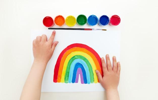 Criança artista. garoto pintando o arco-íris durante a quarentena em casa. instruções de pintura. cartão infantil para enfermeiras Foto Premium