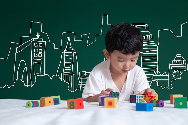 Criança asiática aprendendo brincando com sua imaginação sobre construção e engenheiro desenho de arquitetura e designer Foto Premium