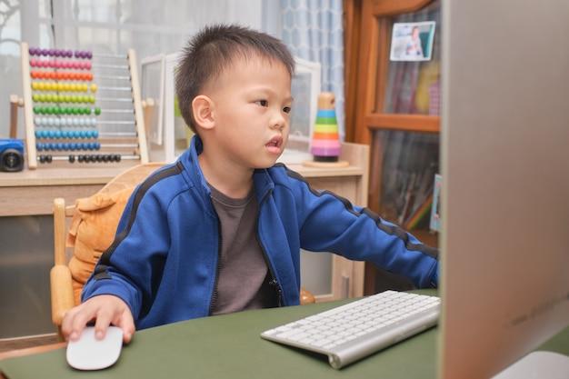 Criança asiática bonitinha com computador pessoal fazendo videochamada em casa, menino do jardim de infância se concentra em estudar online, frequentar a escola por e-learning Foto Premium