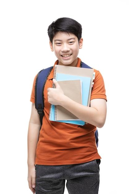 Criança asiática bonito com artigos de papelaria da escola em branco. Foto Premium