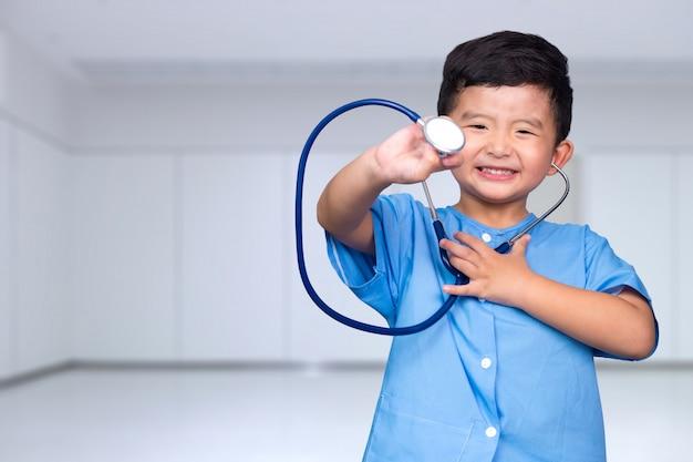 Criança asiática de sorriso no uniforme médico azul que guarda o estetoscópio que olha a câmera, conceito saudável. Foto Premium