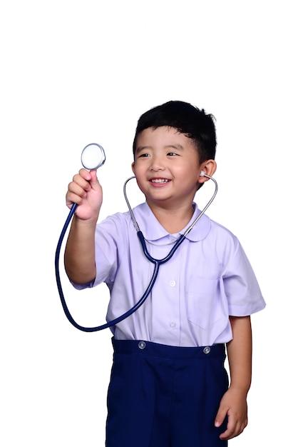 Criança asiática do estudante na farda da escola que joga o estetoscópio médico com trajeto de grampeamento. Foto Premium