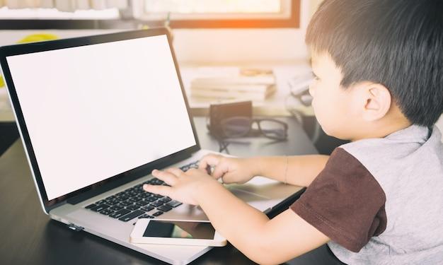Criança asiática está usando um laptop com tela em branco para mock up Foto Premium