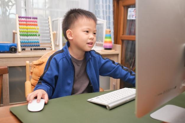 Criança asiática fofa sorridente feliz com computador pessoal fazendo videochamada em casa, menino do jardim de infância estudando online, frequentando a escola via e-learning Foto Premium