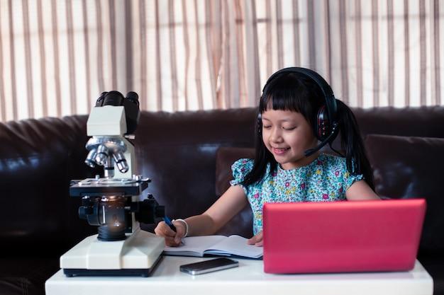 Criança asiática menina usando fones de ouvido, aprendendo on-line usando o laptop e o microscópio em casa, educação a distância Foto Premium