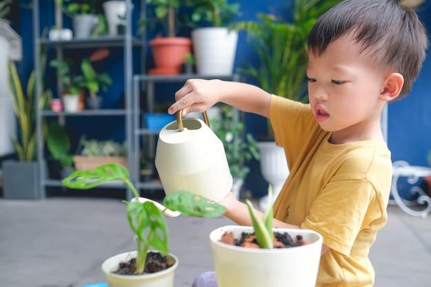 Criança asiática menino criança regar plantas com regador depois de plantar uma árvore jovem no jardim em casa Foto Premium