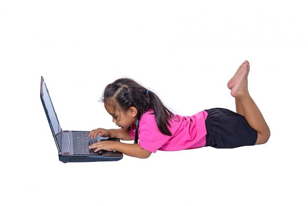 Criança asiática pequena bonito da menina que encontra-se no assoalho que estuda ou que usa o portátil isolado no fundo branco Foto Premium