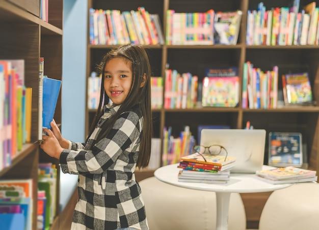 Criança asiática pequena escolhendo livros da estante Foto Premium