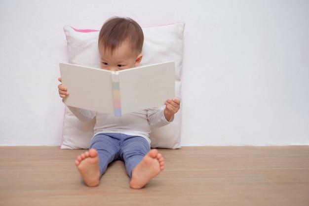 Criança asiática sentada no chão, encostado no travesseiro Foto Premium