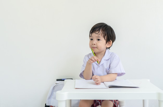 Criança asiática sentado para fazer lição de casa depois da escola Foto Premium