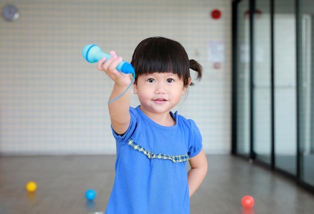 Criança asiática tocando microfone de plástico no quarto do garoto Foto Premium