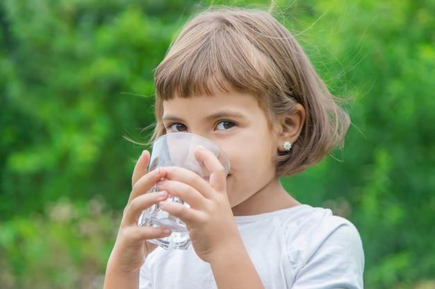 Criança bebe água de um copo Foto Premium