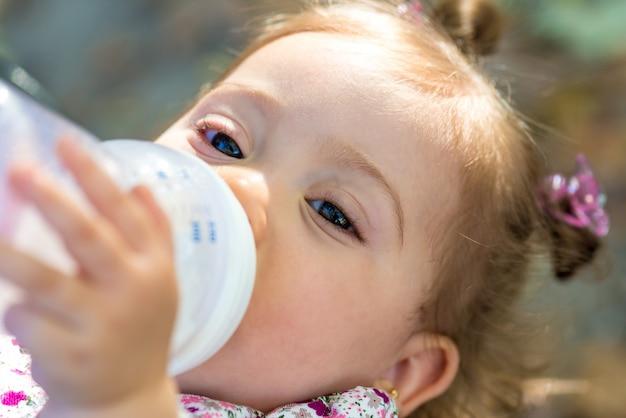 Criança, bebendo, leite, de, mamadeira, ao ar livre Foto Premium