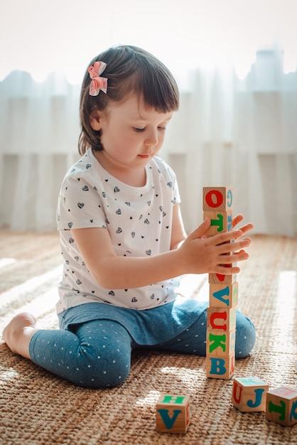 Criança brinca com blocos de madeira com letras no chão da sala uma menina está construindo uma torre em casa ou no jardim de infância. Foto Premium