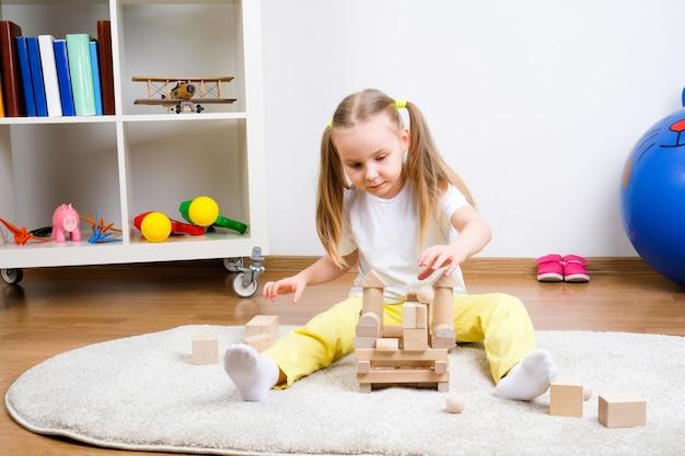 Criança brinca cubos no tapete Foto Premium