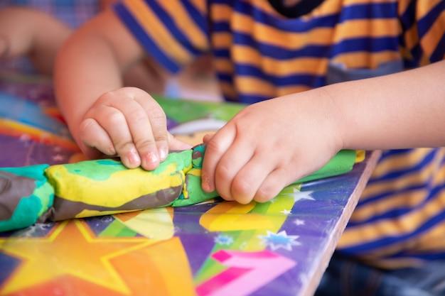 Criança brincando com argila colorida fazendo figuras de animais - closeup nas mãos Foto Premium