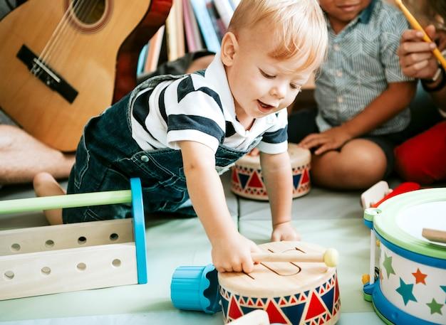 Criança brincando com um conjunto de tambores de madeira Foto Premium