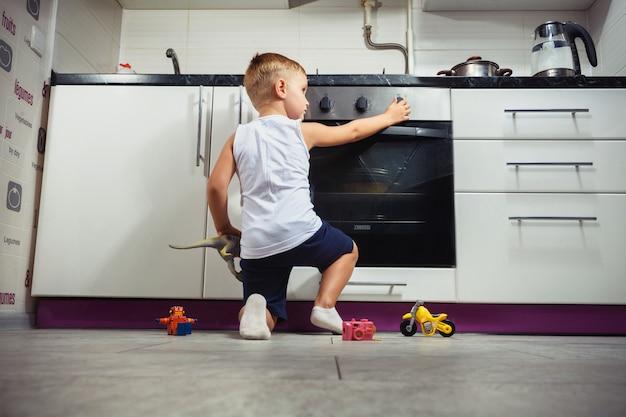 Criança brincando na cozinha com um fogão a gás. Foto Premium