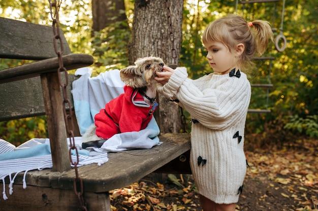 Criança brincar com cachorro engraçado na grande cadeira de madeira no jardim. criança do sexo feminino com cachorrinho posa no quintal. infância feliz Foto Premium