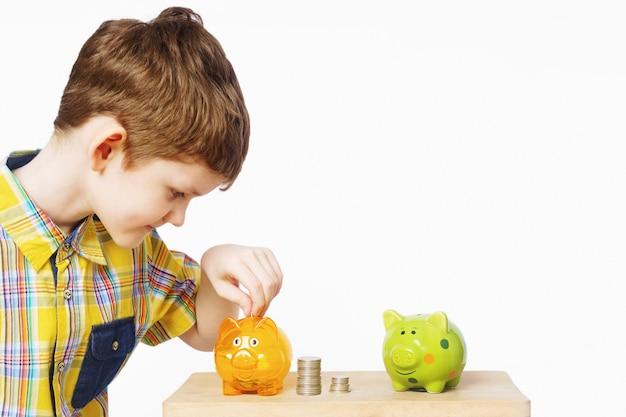 Criança colocando moedas em um cofrinho. Foto Premium