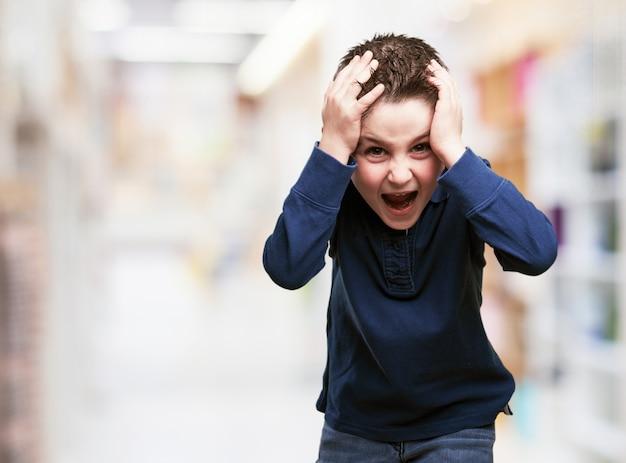 Criança com as mãos na cabeça Foto gratuita