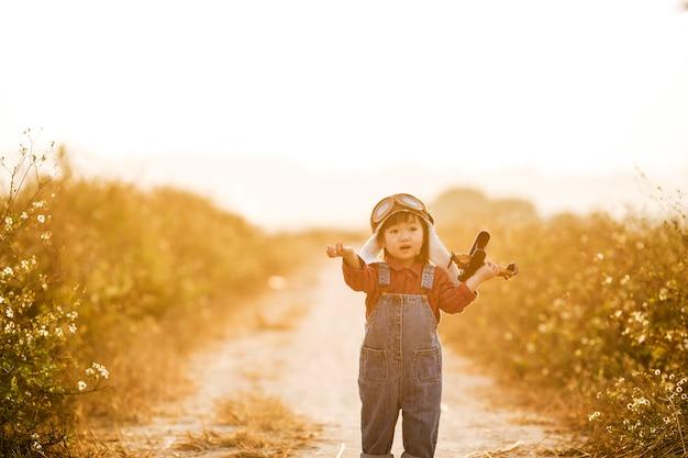 Criança com avião de brinquedo na natureza ao pôr do sol Foto Premium