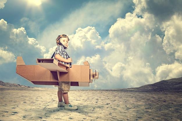 Criança com avião de papelão em um deserto Foto Premium