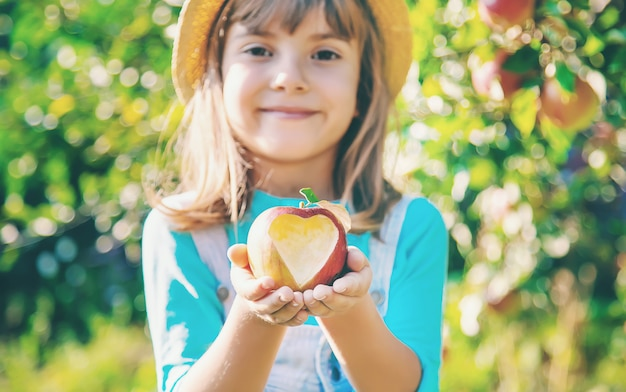 Criança com criança com uma maçã. foco seletivo. Foto Premium