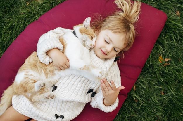 Criança com gato deitado sobre um cobertor no jardim, cuidando dos animais. criança com gatinho posa no quintal. infância feliz Foto Premium