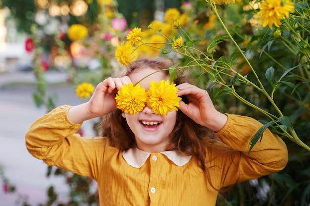Criança com os olhos das flores que mostram os dentes brancos, em ...