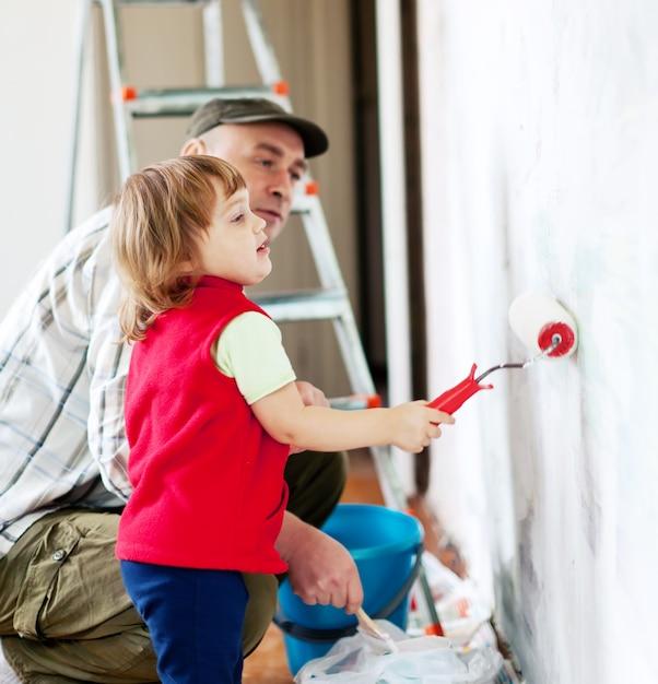 Criança com pai pinta parede Foto gratuita
