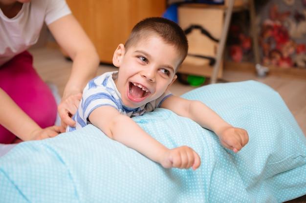 Criança com paralisia cerebral faz terapia musculoesquelética fazendo exercícios Foto Premium