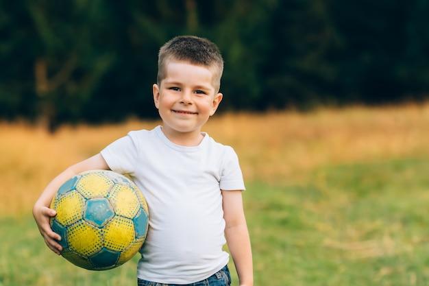 Criança com uma bola de futebol debaixo do braço no jardim de casa com fundo de grama, sorrindo Foto Premium