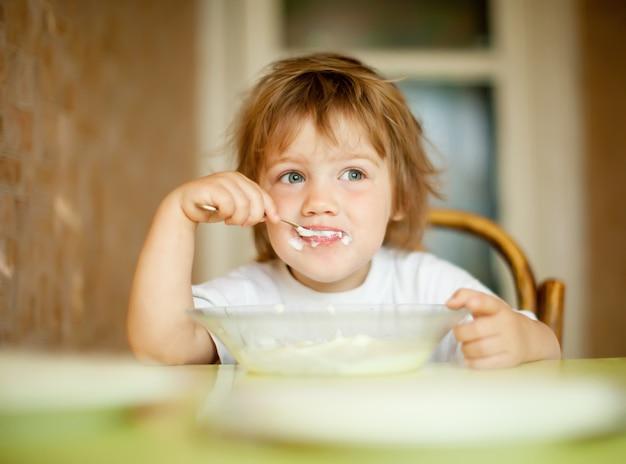 Criança come com colher Foto gratuita