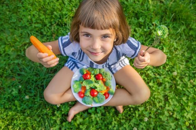 Criança come legumes, brócolis e cenoura Foto Premium