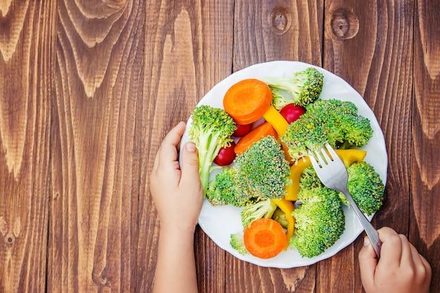 Criança come legumes. foto de verão. foco seletivo. Foto Premium