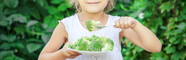 Criança come legumes. foto de verão. foco seletivo Foto Premium