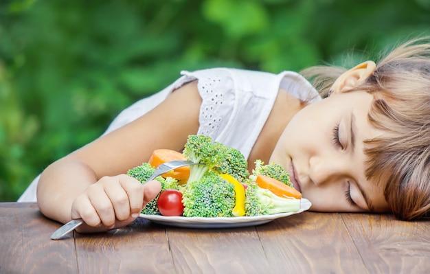 Criança come legumes. Foto Premium