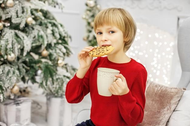 Criança comendo biscoitos de natal e bebendo leite. Foto Premium