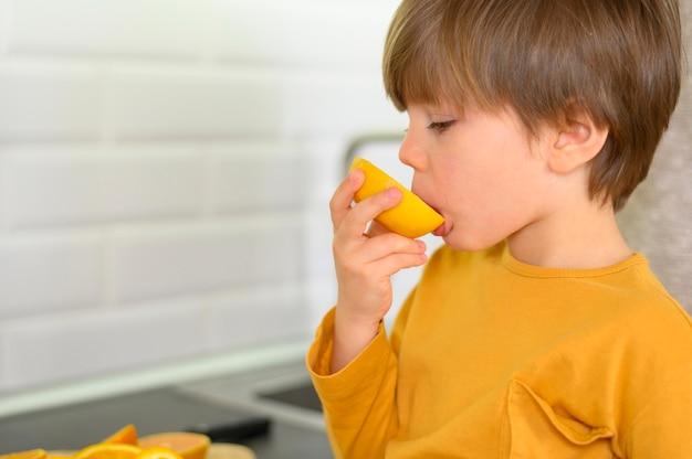 Criança comendo uma laranja na cozinha Foto gratuita