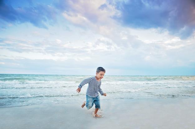 Criança correndo na praia. férias de verão. garoto feliz jogando na praia na hora do sol Foto Premium