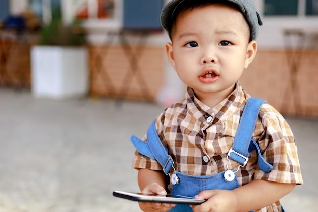 Criança da ásia segurando e tentando jogar smartphone Foto Premium