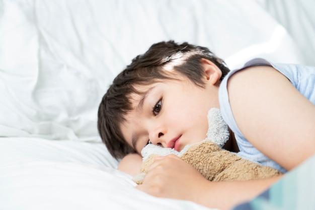 Criança de 7 anos de idade, deitado na cama, criança sonolenta, acordando a manhã em seu quarto com a luz da manhã Foto Premium