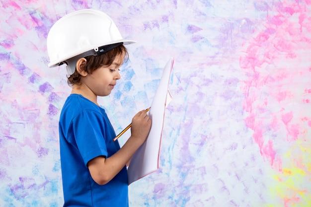 Criança de camiseta azul e capacete branco segurando o plano de papel perto da parede colorida Foto gratuita