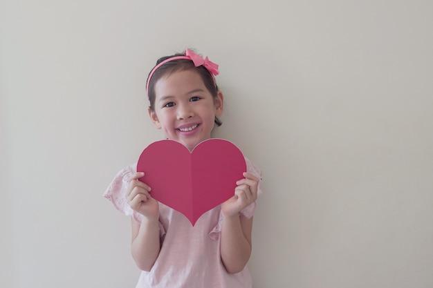 Criança de raça mista segurando coração vermelho grande, saúde do coração, doação, caridade voluntária feliz, responsabilidade social, dia mundial do coração, dia mundial da saúde, dia mundial da saúde mental, bem-estar, conceito de esperança Foto Premium