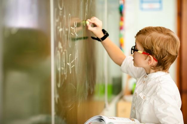 Criança de sete anos com óculos, escrevendo sua lição de casa na escola Foto Premium