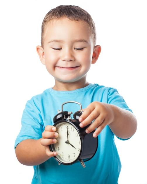 Criança de sorriso que joga com um despertador Foto gratuita