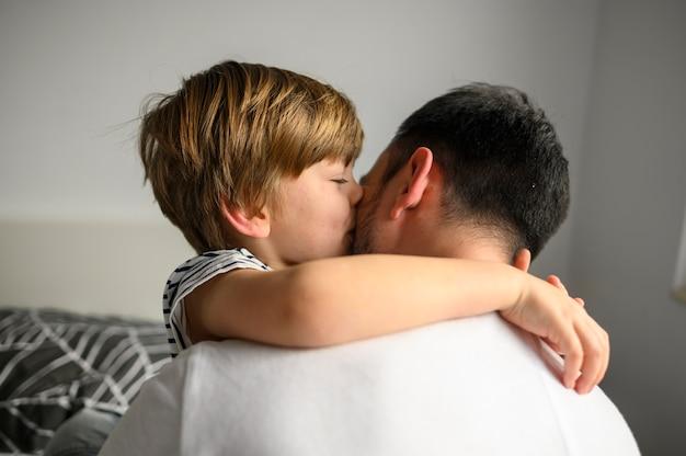 Criança de tiro médio, abraçando seu pai Foto gratuita